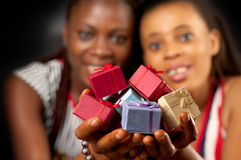 Many colourful presents for you. African American female friends holding many varicolored / varicoloured gifts for you stock photo