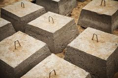 Many concrete blocks arranged in rows for a building foundation. Construction site groundwork background Royalty Free Stock Photo