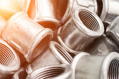 Many of connecting fittings for metal pipes. Small steel castings. Abstract industrial background Royalty Free Stock Images