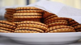 Many cookies with chocolate are lie in white plate covered by napkin stock footage