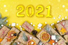 Many craft gift boxes on yellow background. 2021 New Year numbers, wrapped paper presents and garland light