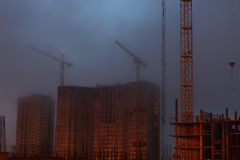 Many cranes on the construction site, unfinished house, foggy evening twilight Royalty Free Stock Images