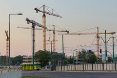 Many cranes on the horizon and a passing tram royalty free stock photos