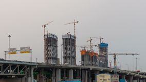 Many of cranes. Tower cranes against blue sky, with clouds. Timelapse stock video