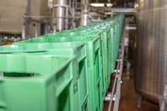 Crates are transported to conveyor belt and moved to the filling line royalty free stock photography
