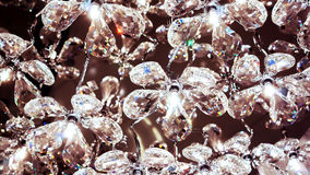 Many crystal clean diamond flowers lay one by one with light inside as part of luxury chandelier Royalty Free Stock Photos