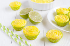 Many cupcakes with yellow cheese cream. Lime and drinking straws on white background. Selective focus Stock Images