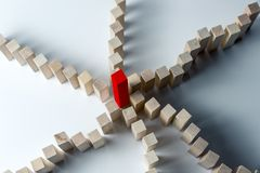 Many curved lines of wooden cubes are combined in the center into one red, as a symbol of queues, a variety of tasks and a leader stock image