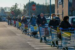 Free Many Customers With Masks Waiting Outside The Grocery Store Before Shopping, Line Of People With Shopping Carts In A Parking Lot Royalty Free Stock Images - 177766989