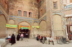 Many customers and women in traditional hijab walking near brick building of Old Market Royalty Free Stock Photos