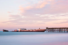 Many Days, Cement Ship. A sunken cement ship sits at the end of a pier near Santa Cruz, California during a colorful sunrise Stock Image
