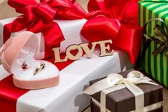 Many decorated gift boxes with ribbon bows and open box. With gold ring Royalty Free Stock Photos
