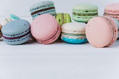 Many delicious macaroons or macaron on a white wooden background close-up, copy space. Many delicious macaroons or macaron on a white wooden background close-up Stock Image