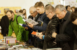 Many different age serious men reading books. KYIV, UKRAINE - APR 21: Many different age serious men reading books of the 6th International Festival BOOK ARSENAL Royalty Free Stock Images