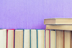 Many different books on violet wall. Stock Photography
