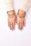 Many different bracelets and rings on hands. Hands with manicure on a white background stock photography