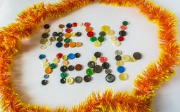 Many different buttons. Buttons for clothes made of plastic. View from above. The buttons write a new year. Around the buttons New Year`s Rain Royalty Free Stock Photography