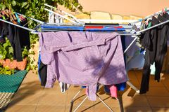 many different clothes holding in washing line at a garden in a sunny day stock photos