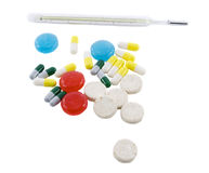 Many different color tablets. Pills and thermometer isolated over white background Royalty Free Stock Photography