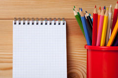 Many different colored pencils and empty notebook on wooden table Stock Images