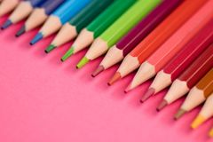 Many Different Colored Pencils Lying on Pink Background in a Wave.  Royalty Free Stock Photography