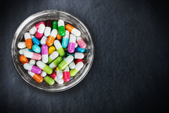 Many different colored pills on a black Royalty Free Stock Photo