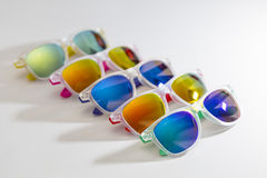 Many different colorful sunglasses in a  diagonal row  on a white background Stock Photo