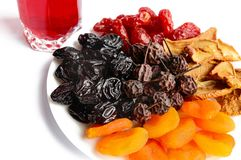 Many different dried fruits dried apricots, apples, pears, prunes on a white plate. And a glass of compote. Isolated on white background. Multivitamin stock images