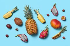 Many different exotic fruits whole and halves presented on a blue background. Flat lay royalty free stock photo