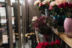 Many different fresh colors in vases on shelves in a flower shop in refrigerators. Stock Photography