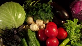 Many different fresh vegetables on a black surface. Fresh vegetables and greens close-up on a black background. Many different fresh vegetables on a black stock video footage