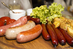Many different fried sausages with salad. On a wooden plate Royalty Free Stock Image