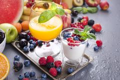 Many different fruits and berries. Vitamins and healthy food. Summer products and orange juice in a glass. Yoghurt and muesli with. Berries. Tasty breakfast royalty free stock photography