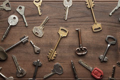 Many different keys on wooden table Royalty Free Stock Photos
