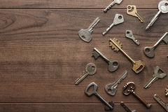Many different keys on wooden table Royalty Free Stock Image