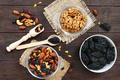 Many different nuts almonds, cashews, walnuts, dried berries blueberries, cranberries, prunes, pumpkin seeds. In bowls on a dark wooden background. Antioxidant Stock Photos