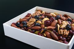 Many different nuts almonds, cashews, walnuts, dried berries blueberries, cranberries. In a white box on a black background. Antioxidant product. Healthy food Stock Image