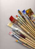 Paint brushes lying on watercolor paper Stock Photos