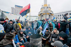 Many different people sitting by the fire on the crowded street during two weeks anti-government protest Royalty Free Stock Image