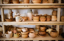 Many different pottery standing on the shelves in a pottery workshop. Low light Royalty Free Stock Photography