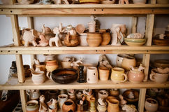 Many different pottery standing on the shelves in a pottery workshop. Low light Royalty Free Stock Photo