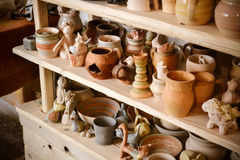 Many different pottery standing on the shelves in a pottery workshop. Low light Royalty Free Stock Image
