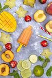 Many different scoops of ice cream. Fresh ingredients for summer beverages and ice cream from mango, carambola, peach, strawberry and lime on a concrete stock image