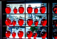 Many different sizes round bottles with red transparent liquid stand on wooden shalved against big window Stock Image