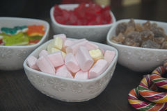 Many different sweets are in white bowls. Royalty Free Stock Images