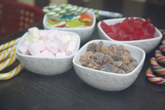 Many different sweets are in white bowls. Stock Photos