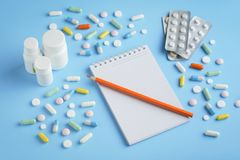 Many different tablets, pills, capsules and notepad with a pencil. stock photo