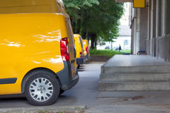 Many different yellow service cars in the parking lot. Side view of yellow delivery vans on parking in front on the entrance a warehouse at distribution center Royalty Free Stock Photography
