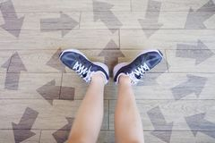 Many Direction Arrow Choices. Selfie of Running Shoes with Drawn Arrows. Woman Violet Sneakers with Decisions on Wooden Floor Back. Ground Great For Any Use Royalty Free Stock Photos