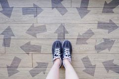 Many Direction Arrow Choices. Selfie of Running Shoes with Drawn Arrows. Woman Violet Sneakers with Decisions on Wooden Floor Back. Ground Great For Any Use royalty free stock photography